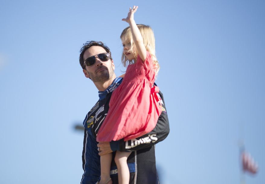 Jimmie Johnson holds his daughter, Genevieve, as they greet fans during driver introductions before the NASCAR Sprint Cub Series auto race in Homestead, Fla., Sunday, Nov. 17, 2013. (AP Photo/J Pat Carter)