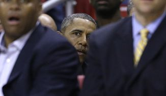 United States President Barack Obama, center, watches the action while sitting behind his brother-in-law, Oregon State head coach Craig Robinson, front left, during the first half of an NCAA college basketball game against Maryland in College Park, Md., Sunday, Nov. 17, 2013. (AP Photo/Patrick Semansky)