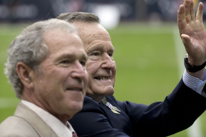 ** FILE ** Former Presidents George H.W. Bush and George W. Bush wave as they drive off the field before an NFL football game abetween the Houston Texans and the Oakland Raiders Sunday, Nov. 17, 2013, in Houston. (AP Photo/Morry Gash)