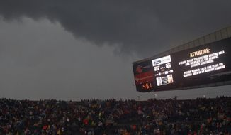 Fans at Soldier Field in Chicago are warned to take cover as a severe storm moves through the area during the first half of an NFL football game between the Chicago Bears and Baltimore Ravens on Sunday, Nov. 17, 2013. (AP Photo/Charles Rex Arbogast)