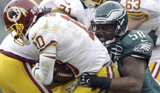Philadelphia Eagles outside linebacker Trent Cole sacks Washington Redskins quarterback Robert Griffin III during the second half of an NFL football game in Philadelphia, Sunday, Nov. 17, 2013. (AP Photo/Matt Rourke)