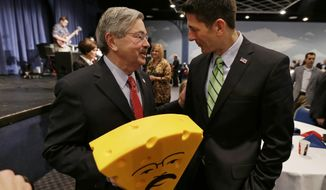 Rep. Paul Ryan (right), Wisconsin Republican, talks with Iowa Gov. Terry Branstad after presenting him with a cheesehead hat during Mr. Branstad's birthday bash and fundraiser on Saturday, Nov. 16, 2013, in Altoona, Iowa. (AP Photo/Charlie Neibergall)