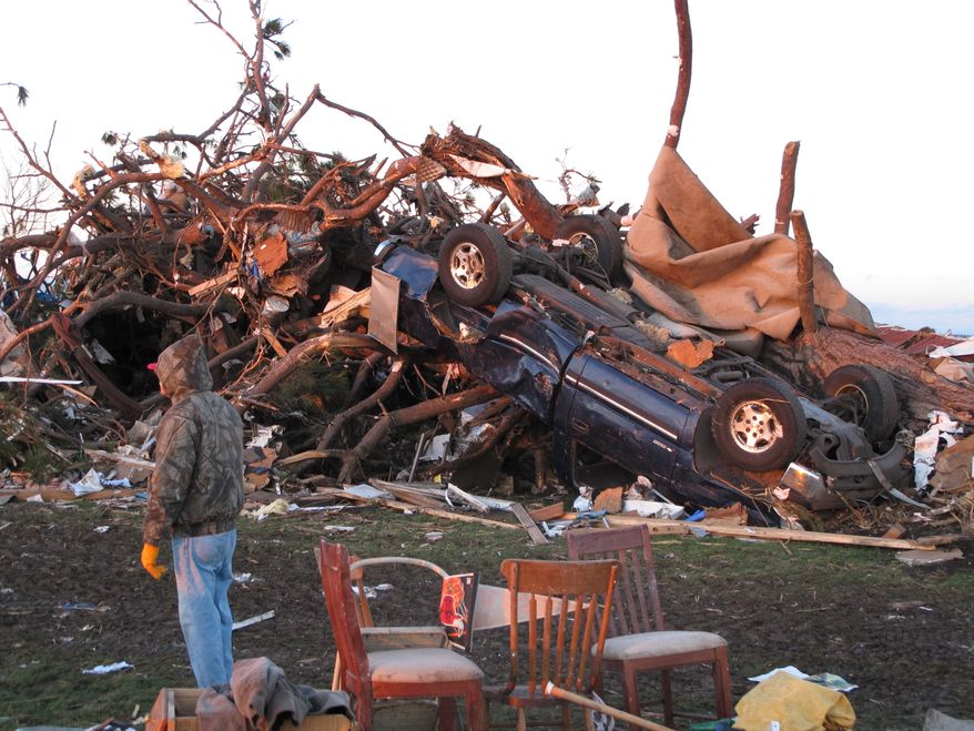 A man stands near a pickup that belonged to farmer Curt Zehr after a tornado blew through Zehr's farm on Sunday, Nov. 17. 2013. The farm destroyed Zehr's home just outside Washington, Ill., and caused extensive damage in the town. Zehr's wife and son were at home at the time but were not injured. Dozens of Zehr's friends and neighbors helped look through the rubble. (AP Photo/David Mercer)