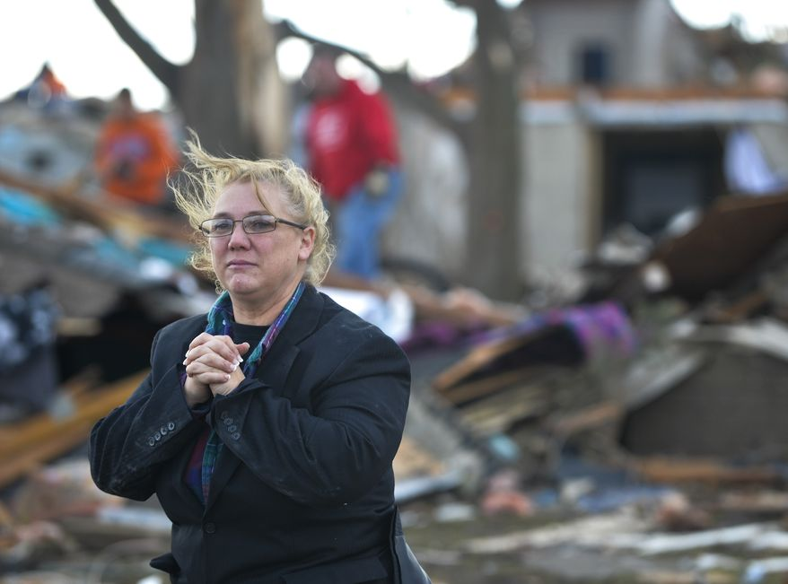 A resident of Washington, Ill., surveys the damage to her home and neighbors after a tornado and severe thunderstorms swept through a portion of the town on Sunday, Oct. 17, 2013. (AP Photo/Peoria Journal Star, Ron Johnson)