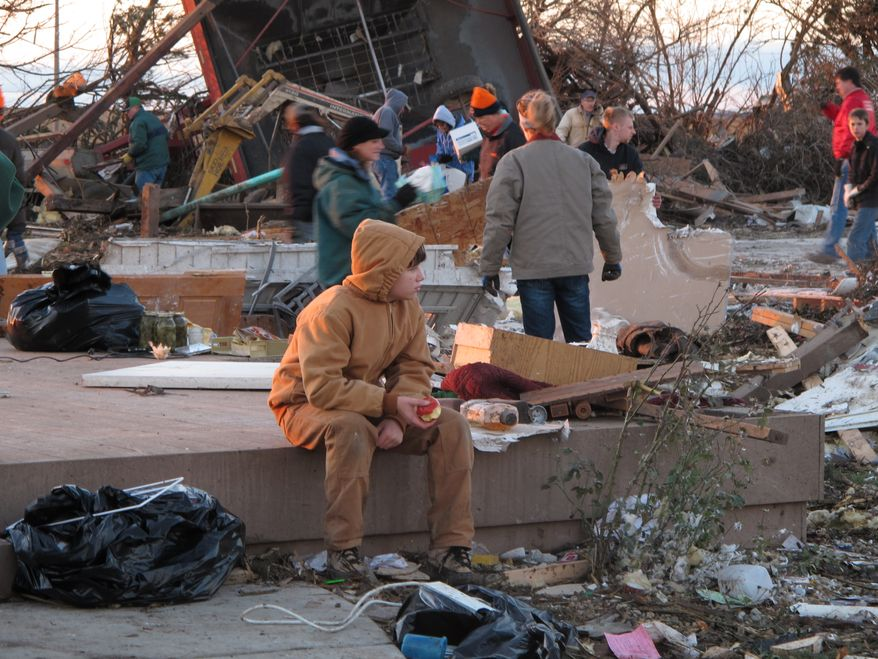 A young boy takes a break from helping comb the rubble of Curt Zehr's home just outside Washington, Ill., on Sunday, Nov. 17, 2013. Zehr's wife and adult son took shelter in their basement as a tornado destroyed their farm house they were not injured. The tornado cut a path of destruction through Washington. (AP Photo/David Mercer)