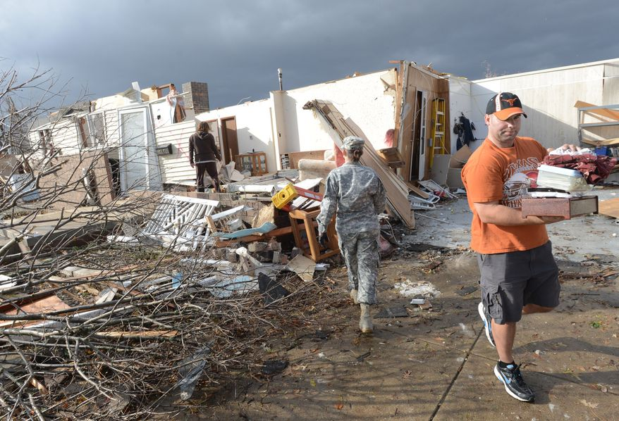 US Army National Guard Master Sergeant Katie Williams of Altamont, center, walks to a destroyed home of Barb and John Evans in the Devonshire Subdivision in Washington, Illinois as relatives rescue belongings after a tornado destroyed several homes on Sunday, Nov. 17, 2013. (AP Photo/The Pantagraph, Steve Smedley)