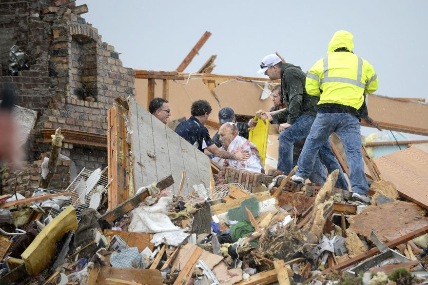 Rescuers pull an injured resident from a demolished house after a tornado destroyed parts of Washington, Ill., Sunday, nov. 17, 2013. (AP Photo/Journal Star, David Zalaznik)  MANDATORY CREDIT