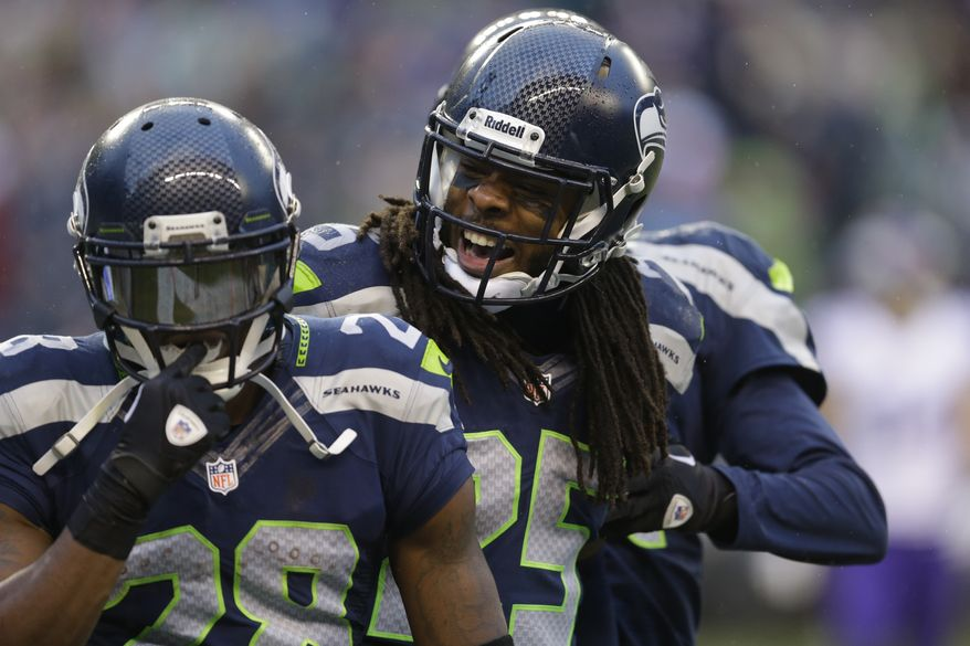 Seattle Seahawks' Richard Sherman, right, congratulated Walter Thurmond after Thurmond's interception and touchdown against the Minnesota Vikings in the second half of an NFL football game, Sunday, Nov. 17, 2013, in Seattle. (AP Photo/Ted S. Warren)