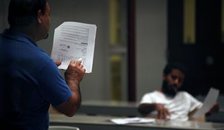 """A Guantanamo detainee sits in on a """"life skills"""" seminar at the detention facility at Guantanamo Bay, Cuba. A multimillion-dollar federal contract allows prisoners to enroll in seminars to learn all about basic landscaping and pruning, calligraphy and Microsoft PowerPoint while the U.S. tries to figure out what to do with them. (Associated Press)"""