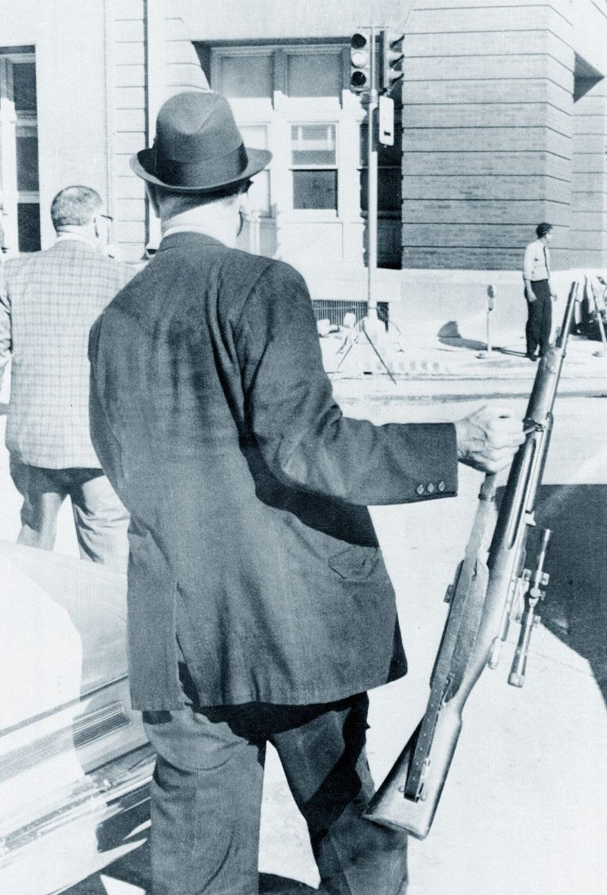 A plainclothes Dallas policeman carries the rifle used that day in the assassination of President Kennedy.    Associated Press photo