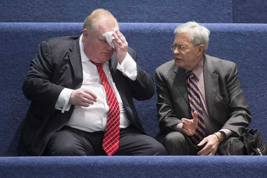 """Toronto Mayor Rob Ford, left,  sits with his lawyer George Rust-D'Eye in the council chamber as councillors look to pass motions to limit his powers at city hall in Toronto on Monday, Nov. 18, 2013. Blasting what he called a """"coup d'etat,"""" Ford said voters should be able to pass judgment on him, not his fellow councillors.  (AP Photo/The Canadian Press, Chris Young)"""