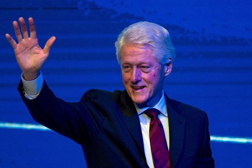 Former President Bill Clinton waves after speaking at a forum in Beijing in Monday, Nov. 18, 2013. (AP Photo/Ng Han Guan)