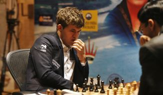 Norway's Magnus Carlsen, left, plays against reigning world chess champion India's Viswanathan Anand during the Chess World Championship match in Chennai, India, Monday, Nov. 18, 2013. The 43- year old Anand  has the advantage of playing at home in India, where he is treated as a super star. The 22-year-old Carlsen is the top Western player since Bobby Fischer in a game that has traditionally been dominated by Russians, and chess enthusiasts hope his mass-market appeal can win over new fans and help boost interest worldwide. (AP Photo/Arun Sankar K )