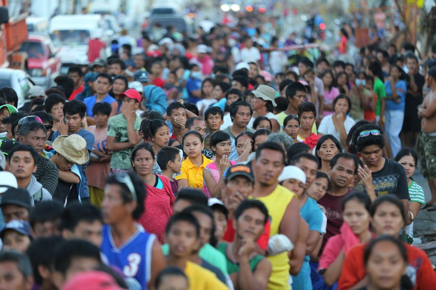 Typhoon survivors queue during the distribution of relief goods in typhoon-hit Tacloban, Leyte province, central Philippines Monday, Nov. 18, 2013. Corruption is a concern after any major natural disaster, as millions of dollars in cash and goods rush in from around the world. But those worries are especially acute in the Philippines, where graft has been a part of life for decades. (AP Photo/Aaron Favila)
