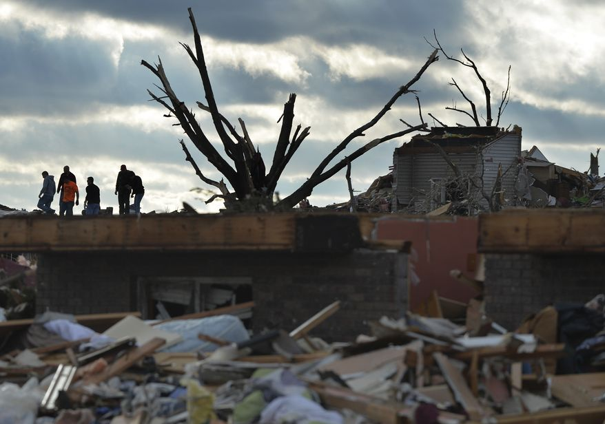 Residents search through a neighborhood in Washington, Ill., after a tornado and strong thunderstorms  swept through the north part of the town destroying several homes on Sunday, Nov. 17, 2013. (AP Photo/Peoria Journal Star, Ron Johnson) MANDATORY CREDIT