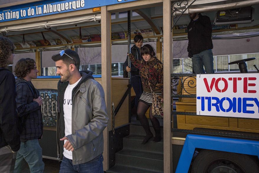 "** FILE ** University of New Mexico students exit the ""Voting Trolly"" at a stop on campus in Albuquerque, N.M., on Tuesday, Nov. 14, 2013. ABQ Trolley Co. partnered up with the nonprofit Progress Now New Mexico to provide University of New Mexico students transportation to voting sites due to a prior vote by the Albuquerque City Council that excluded the university as a voting site for a special ballot. Albuquerque voters will decide whether to ban abortions after 20 weeks following an emotional and graphic campaign that has included protests and hundreds of thousands of dollars on television and radio ads that have brought out more than twice as many early voters as the recent mayoral elections. (AP Photo/Juan Antonio Labreche)"