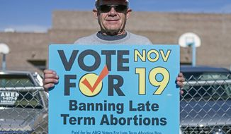 Monte Harms, of Albuquerque, N.M., advocates Albuquerque's late term abortion ban outside of a voting site at Eisenhower Middle School in Albuquerque, N.M., Tuesday, Nov. 19, 2013. Albuquerque voters will decide whether to ban abortions after 20 weeks following an emotional and graphic campaign that has included protests and hundreds of thousands of dollars on television and radio ads that have brought out more than twice as many early voters as the recent mayoral elections. (AP Photo/Juan Antonio Labreche)