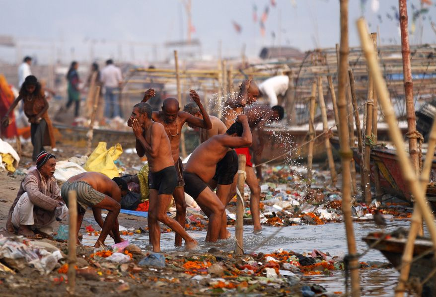 Indian Hindu devotees performs evening rituals after a holy dip at Sangam, the confluence of the Ganges, Yamuna and the mythical Saraswati River, in Allahabad India,  Monday, Nov. 18, 2013. Allahabad in the northern Uttar Pradesh state is an important Hindu pilgrimage center. (Associated Press)