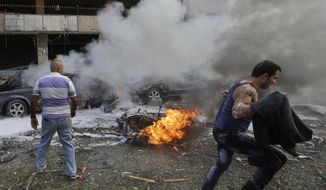 A Lebanese man runs in front of a burned car, at the scene where two explosions have struck near the Iranian Embassy killing many, in Beirut, Lebanon, Tuesday Nov. 19, 2013. The blasts in south Beirut's neighborhood of Janah also caused extensive damage on the nearby buildings and the Iranian mission. The area is a stronghold of the militant Hezbollah group, which is a main ally of Syrian President Bashar Assad in the civil war next door. It's not clear if the blasts are related to Syria's civil war. (AP Photo/Hussein Malla)