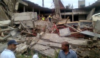 The scene of a mall that collapsed in Tongaat, South Africa, Tuesday, Nov. 19, 2013. South African police say one person has died and several were injured in a roof collapse at a shopping mall that was under construction. The accident happened Tuesday in Tongaat, near the eastern coastal city of Durban, and rescue teams rushed to the scene to help workers who were trapped beneath the rubble. (AP Photo/Neil Powell,Crisis Medical)