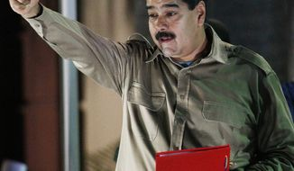 Venezuela's President Nicolas Maduro holds the documents granting him emergency decree powers as he gestures to supporters at Miraflores presidential palace in Caracas, Venezuela, Tuesday, Nov. 19, 2013.  Venezuela's congress granted Maduro emergency decree powers that will allow him to approve laws without consulting congress for up to a year. (AP Photo/Ariana Cubillos)