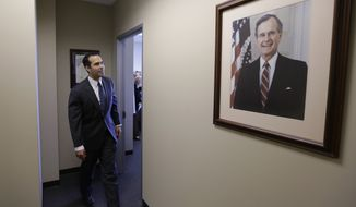 George P. Bush passes a portrait of his grandfather, George H.W. Bush, as visits the Republican Party of Texas headquarters where he formally filed to run for Texas land commissioner, Tuesday, Nov. 19, 2013, in Austin, Texas. Bush will face former El Paso Democratic Mayor John Cook in next November's election. (AP Photo/Eric Gay)