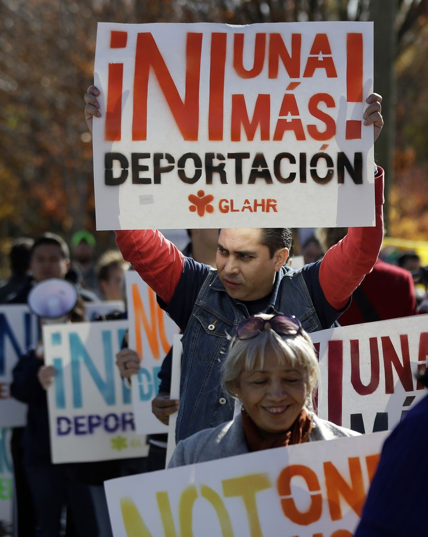A man marches with a sign during a protest in front of a building that houses federal immigration offices Tuesday, Nov. 19, 2013, in Atlanta.  Eight immigration activists, protesting deportations of people who are in the country illegally, were taken into custody by police after they locked arms and some of them chained themselves to the gates outside immigration offices..   (AP Photo/John Bazemore)