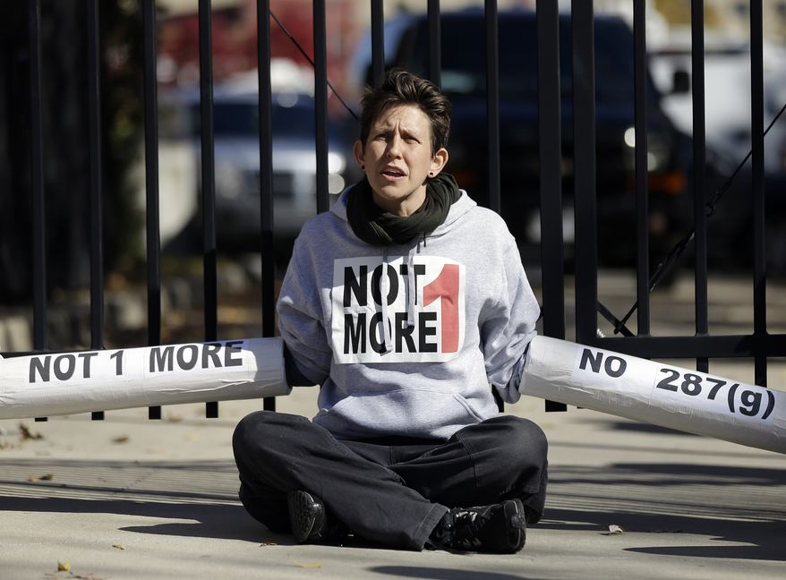 An Immigration activist, protesting deportations of people who are in the country illegally, blocks the front gate of a building that houses federal immigration authorities Tuesday, Nov. 19, 2013, in Atlanta. Eight immigration activists were taken into custody after they locked arms and some of them chained themselves to the gates outside the offices. Information on possible charges faced by the protesters wasn't immediately available.  (AP Photo/John Bazemore)