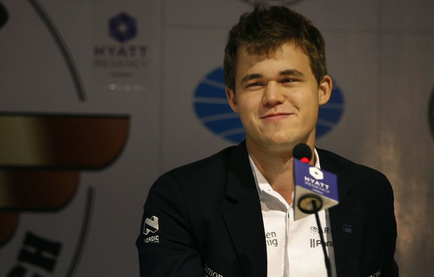 ** FILE ** Norway's Magnus Carlsen interacts with the media after a match against reigning world chess champion Viswanathan Anand of India during the chess world championship match in Chennai, India, Tuesday, Nov. 19, 2013. Carlson, 22, is the top Western player since Bobby Fischer in a game that has traditionally been dominated by Russians, and chess enthusiasts hope his mass-market appeal can win over new fans and help boost interest worldwide. (AP Photo/Arun Sankar K )