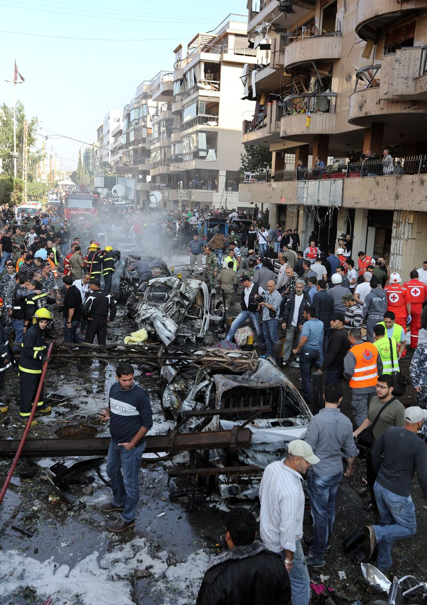 Lebanese people gather at the scene where two explosions have struck near the Iranian Embassy killing many, in Beirut, Lebanon, Tuesday, Nov. 19, 2013. The blasts in south Beirut's neighborhood of Janah also caused extensive damage on the nearby buildings and the Iranian mission. The area is a stronghold of the militant Hezbollah group, which is a main ally of Syrian President Bashar Assad in the civil war next door. It's not clear if the blasts are related to Syria's civil war. (AP Photo/Bilal Hussein)