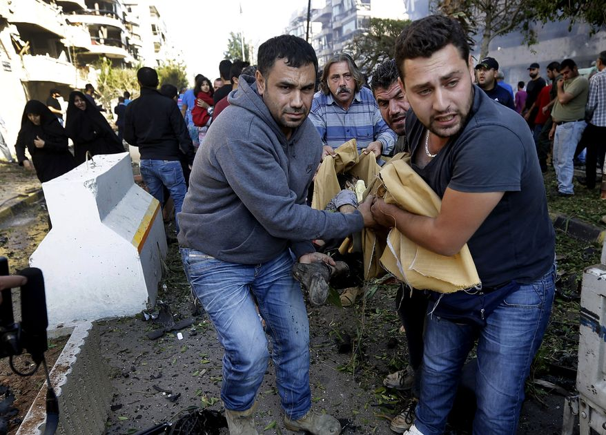 Lebanese citizens carry a dead body, at the scene where two explosions have struck near the Iranian Embassy killing many, in Beirut, Lebanon, Tuesday Nov. 19, 2013. The blasts in south Beirut's neighborhood of Janah also caused extensive damage on the nearby buildings and the Iranian mission. The area is a stronghold of the militant Hezbollah group, which is a main ally of Syrian President Bashar Assad in the civil war next door. It's not clear if the blasts are related to Syria's civil war. (AP Photo/Hussein Malla)