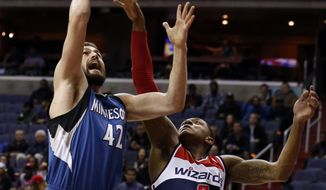 Minnesota Timberwolves forward Kevin Love (42) shoots past Washington Wizards guard Bradley Beal (3) in the first half of an NBA basketball game Tuesday, Nov. 19, 2013, in Washington. (AP Photo/Alex Brandon)