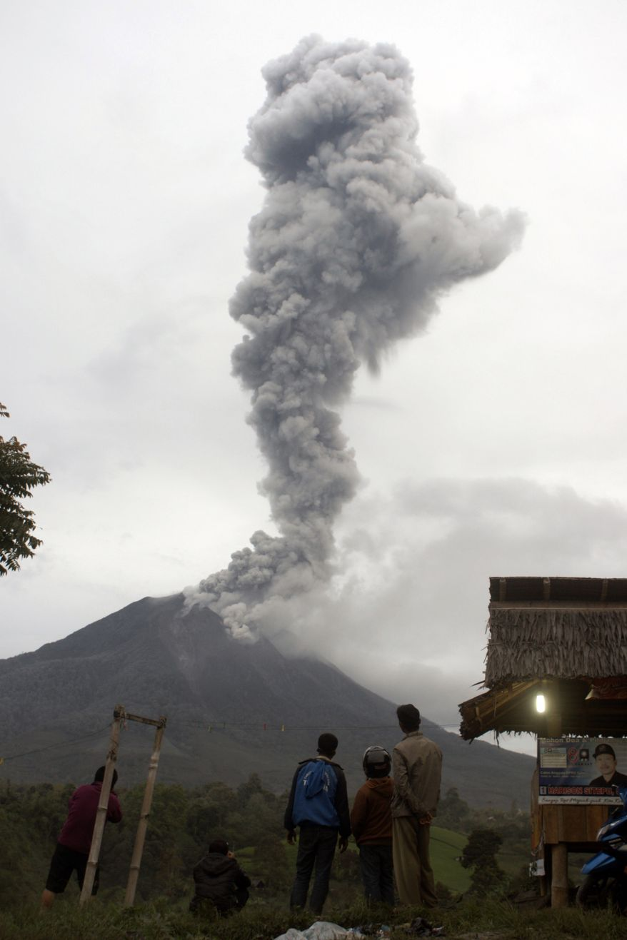 Villagers watch Mount Sinabung spewing volcanic ash in Tiga Pancur, North Sumatra, Indonesia, Wednesday, Nov. 20, 2013. The 2,600-meter (8,530-foot) -high mountain has sporadically erupted since September after being dormant for three years. (AP Photo/Mafa Yuli Ramadhani)