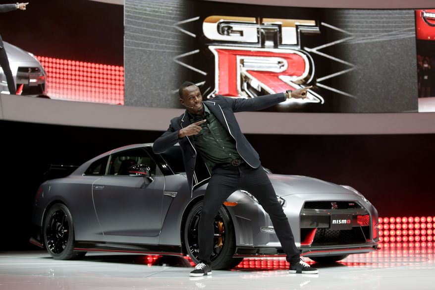 Olympic gold medalist, Usain Bolt poses in front of the the 2015 Nissan GT-R is debuted at the Los Angeles Auto Show in Los Angeles, Wednesday, Nov. 20, 2013. (AP Photo/Chris Carlson)