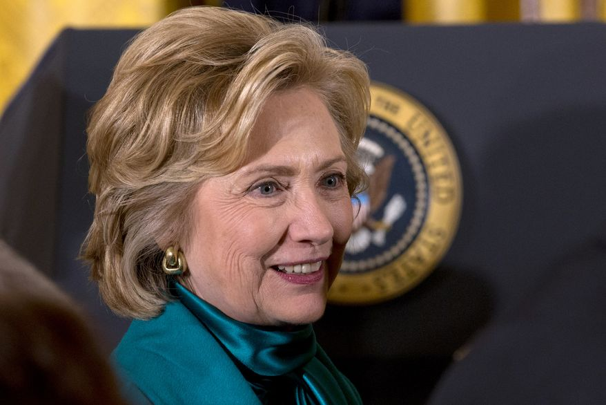 Former Secretary of State Hillary Rodham Clinton walks past the Presidential seal in the East Room of the White House in Washington, Wednesday, Nov. 20, 2013, after a ceremony where President Barack Obama awarded the Presidential Medal of Freedom to former President Bill Clinton and others. (AP Photo/Jacquelyn Martin)