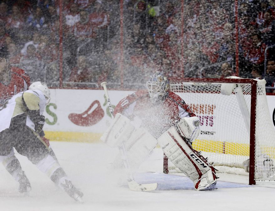Pittsburgh Penguins left wing Chris Kunitz (14) sprays ice on Washington Capitals goalie Braden Holtby (70) in the second period of an NHL hockey game, Wednesday, Nov. 20, 2013, in Washington. The Penguins won 4-0. (AP Photo/Alex Brandon)
