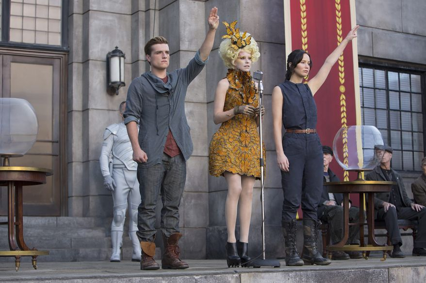 """Josh Hutcherson, Elizabeth Banks (center) and Jennifer Lawrence are back for more """"Hunger Games"""" in a fiery sequel cooked up for adolescent appetites. (Lionsgate via Associated Press)"""