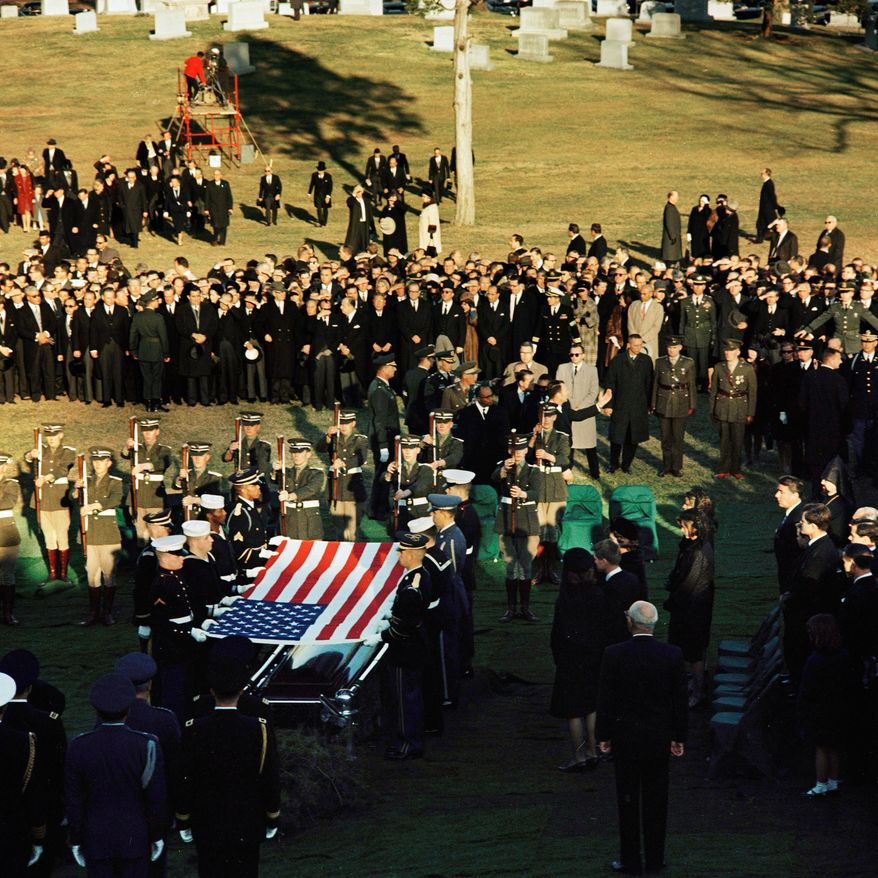 FILE - In this Nov. 25, 1963 file photo, an Irish cadet honor guard, center rows holding rifles, stands in formation as the U.S. flag is lifted from the coffin of President John F. Kennedy during his funeral services at Arlington National Cemetery in Arlington, Va. (AP Photo)