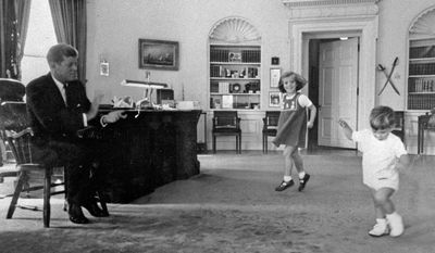 """FILE - In this October 1962 file photo provided by the White House, President John F. Kennedy, left, claps time as his children Caroline, center, and John, Jr. dance in the Oval Office. Asked in 2012 if she ever felt overwhelmed by the legacy of the Kennedy years and the carefully cultivated image of a modern day Camelot, Kennedy said, """"I can't imagine having better parents and a more wonderful brother. So I feel really fortunate that those are my family, and I wish they were here. (AP Photo/White House, File)"""