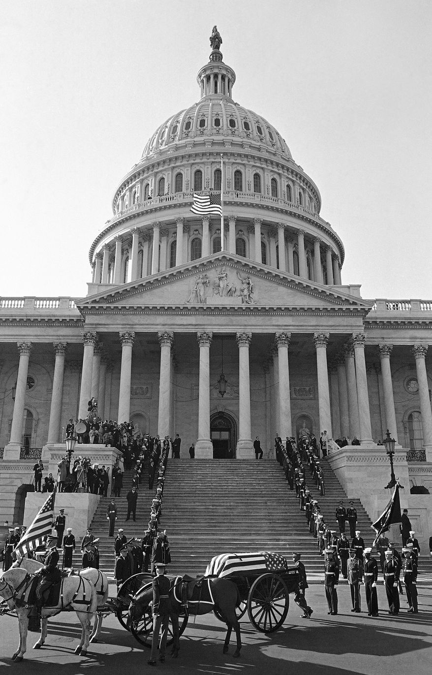FILE - In this Sunday, Nov. 24, 1963 file photo, the casket of President John F. Kennedy reaches the Capitol in Washington on a horse-drawn caisson, accompanied by a symbolic riderless horse named Black Jack, with boots reversed in the stirrups, symbolizing a fallen leader. (AP Photo)