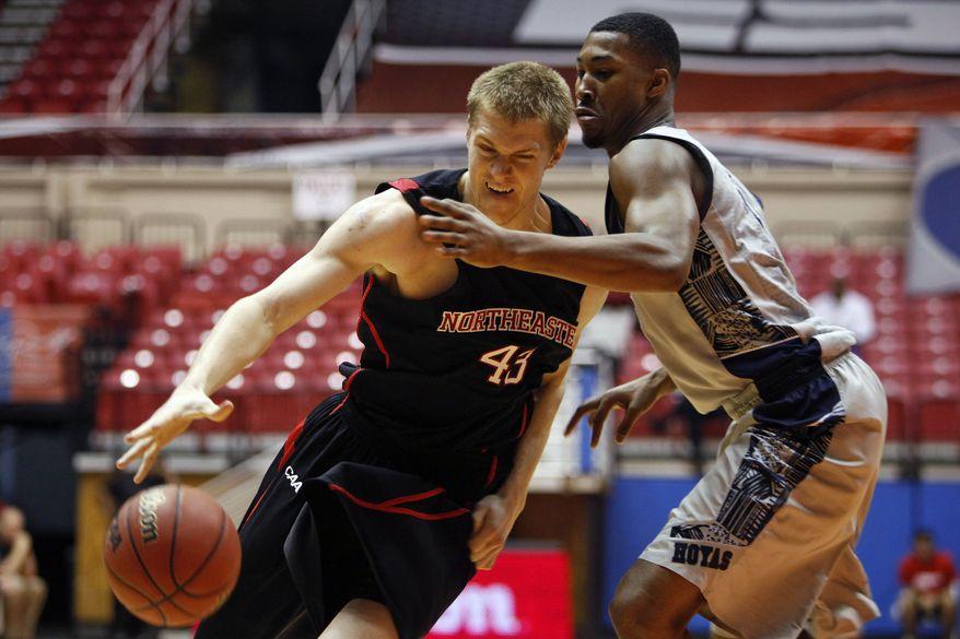 Northeastern forward Scott Eatherton, left, drives the ball against Georgetown's Mikael Hopkins during a NCAA college basketball game in San Juan, Puerto Rico, Thursday, Nov. 21, 2013. (AP Photo/Ricardo Arduengo)