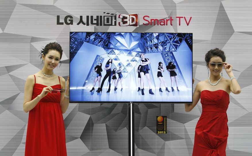 Models pose with a Cinema 3-D smart TV during a press conference to introduce the LG Electronics television and the company's marketing strategy for 2012 on Thursday, Jan. 19, 2012, in Seoul. (AP Photo/Ahn Young-joon)