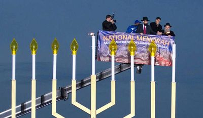 This Dec. 20, 2011, file photo shows Office of Management and Budget  Director Jacob Lew, second from right, Rabbi Levi Shemtov, second from left, and Rabbi Abraham Shemtov, right, as they light the National Hanukkah Menorah during a ceremony on The Ellipse in Washington marking the first night of Hanukkah. (AP Photo/Manuel Balce Ceneta, file)