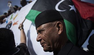 A Libyan man watches a protest against the Tripoli-based militias and supporting the new national army and the police corps in the Libyan capital Friday, Nov. 22, 2013. Thousands of protesters have gathered in Libya's capital to call on unlawful armed groups to leave the city, a week after militiamen killed more than 40 people. The head of Tripoli's local council, Al-Sadat al-Badri, told the crowd on Friday that the city will remain on strike until the capital and its surroundings are free of militias. (AP Photo/Manu Brabo)