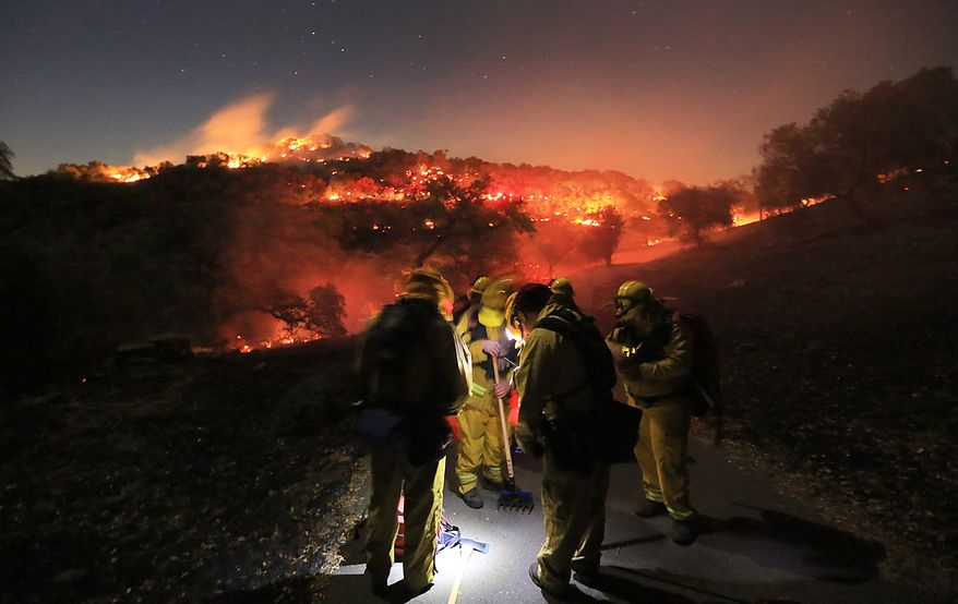 Firefighters from Schell Vista of Sonoma County and Santa Clara County Cal Fire prepare to put out hotspots on a fire in the hills of Soda Canyon above Napa, Calif., Friday, Nov. 22, 2013.  The fire grew to over 300 acres by daybreak, fanned by high winds. (AP Photo/Santa Rosa Press Democrat, Kent Porter)