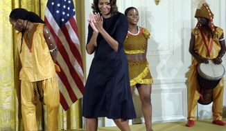 ** FILE ** First lady Michelle Obama walks on stage after watching the children from the Kuruka Maisha Foundation, an arts school in Nairobi, Kenya, perform in the East Room of the White House in Washington, Friday, Nov. 22, 2013. (AP Photo/Susan Walsh)