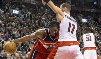 Washington Wizards Nene, left, drives at Toronto Raptors' Jonas Valanciunas during the first half of an NBA basketball game in Toronto on Friday, Nov. 22, 2013. (AP Photo/The Canadian Press, Chris Young)
