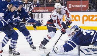 Toronto Maple Leafs goaltender James Reimer, right, makes a save at the feet of Washington Capitals right winger Troy Brouwer as Maple Leafs defenseman Jake Gardiner, left, and center Peter Holland close in during third period NHL hockey action in Toronto, Saturday, Nov. 23, 2013. Toronto won 2-1. (AP Photo/The Canadian Press, Chris Young)
