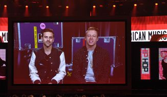 "Macklemore (right) and Ryan Lewis accept the award for favorite album-rap/hip-hop for ""The Heist"" via satellite from Miami during the American Music Awards at the Nokia Theatre L.A. Live on Sunday, Nov. 24, 2013, in Los Angeles. (John Shearer/Invision/AP)"