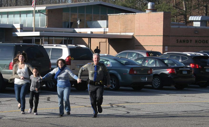 ** FILE ** A police officer leads two women and a child from Sandy Hook Elementary School in Newtown, Conn., where a gunman opened fire, killing 26 people, including 20 children, on Friday, Dec. 14, 2012. (AP Photo/Newtown Bee, Shannon Hicks)